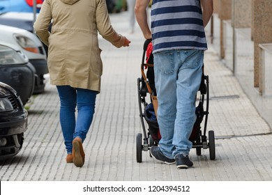 married couple walking with a baby carriage on the street