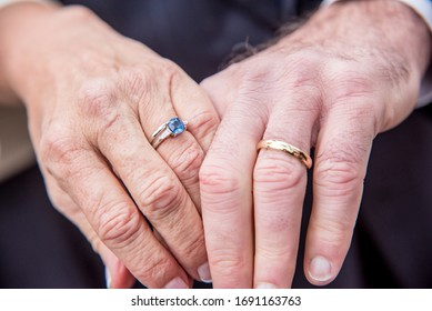 Married elderly couple - close up of two hands holding each other wearing wedding rings.