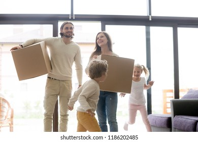 Married millennial couple enter living room with little children. Family moving at new house. Young smiling parents holding cardboard boxes, joyful toddler son and daughter running and playing around
