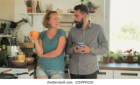 married people in the kitchen. Upset woman with boyfriend at home. handsome hipster and attractive blond fall aboard. family quarrel drinking coffee in apartment