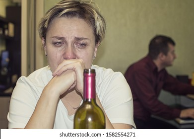 a married woman cries and drinks alcohol. female alcoholism.selective focus. film grain.