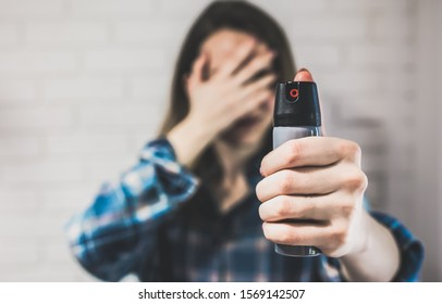Married woman is holding pepper spray canister for personal protection. Girl covers her face with hands. White background behind. Self-defense photo. Copy space place.