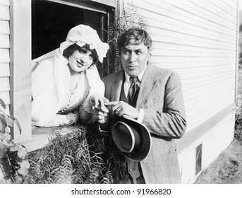 Married woman leaning out of a window to her husband