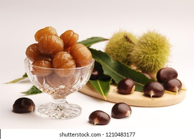 marron glaces, candied chestnuts in a glass bowls, decorated with raw chestnuts