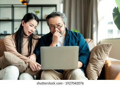 heiraten asiatische Ehepaare zu Hause Finanzen, überprüfen ihre Bankkonten mit Laptop und Taschenrechner im Wohnzimmer.asiatisches Paar sitzend auf Sofa mit Laptop und stressige Emotion zu Hause