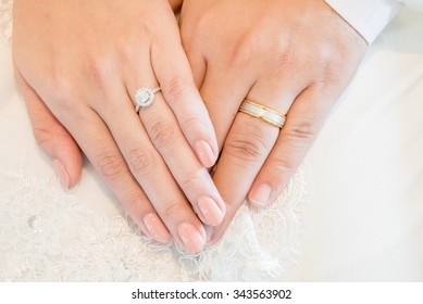 Marry me, Moment of LOVE, hands of a wedding heterosexual couple. Groom put a ring on finger of his lovely wife. - Selective focus.