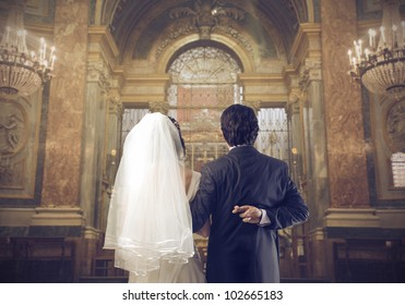 Marrying couple in a church with groom crossing his fingers behind his back