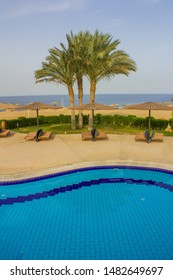 Marsa Alam, Egypt - May 11, 2019: luxury beach Egypt against the background of the beauty of the sea with coral reefs. Sunny resort beach with umbrella and beach chairs at the