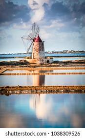 Marsala, Italy. Stagnone Saline Lagoon with vintage windmills and saltwork, Trapani province, Sicily.