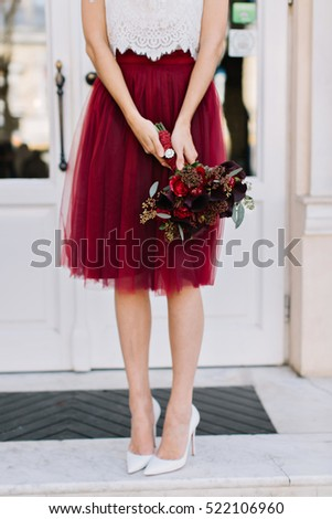 a3319b3ab Marsala tulle skirt, bouquet of flowers in hands of slim girl on street