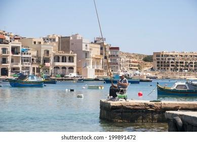 Marsaskala, Malta - May 31: Fisherman fishing in a bay at Marsaskala city, Malta in May 31, 2014