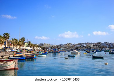 Marsaxlokk historic harbor full of wooden boats in Malta. Blue sky and village background. Destination for vacation, relaxing and fishing.