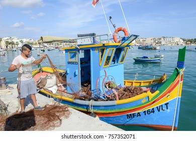 Marsaxlokk, Malta - 3 November 2017: fishermen preparing the fishing nets near their boat at Marsaxlokk on Malta