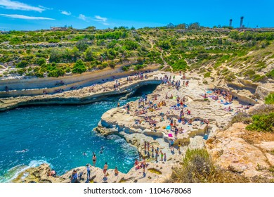 MARSAXLOKK, MALTA, APRIL 30, 2017: People are enjoying sunny day at Saint Peter's pool near Marsaxlokk, Malta