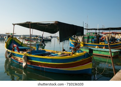MARSAXLOKK, MALTA - AUGUST 23, 2017: Traditional colorful luzzu fishing boats arriving and anchoring early in the morning in Marsaxlokk village harbor