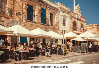 MARSAXLOKK, MALTA: Crowd of people sitting at local restaurants, waiting for food on sunny and historical city street on 20 October, 2019. Malta has more than 1.6 million tourists per year