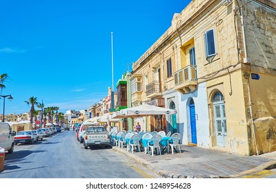 MARSAXLOKK, MALTA - JUNE 18, 2018: Walk along the Xatt Is-Sajjieda promenade with a view on historic edifices, tourist cafes and souvenir stores, on June 18 in Marsaxlokk.