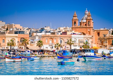 Marsaxlokk, Malta. Luzzu traditional eyed colorful boats in the harbor of fishing village, Mediterranean Sea.