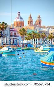 Marsaxlokk, Malta - May 05, 2016: Luzzu anchored in Malta, at the port of Marsaxlokk, a traditional fishing village in Malta. A luzzu is a traditional fishing boat, painted in bright colours.