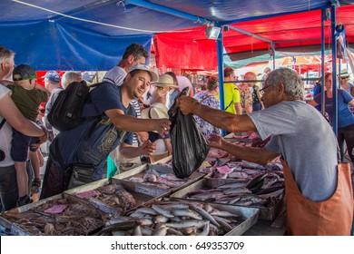 MARSAXLOKK, MALTA - May 28, 2017: A man in a fish market buys some fish