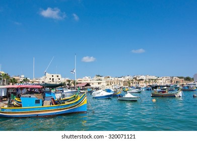 MARSAXLOKK, MALTA - SEPTEMBER 15, 2015: Colorful painted small boats moored in the clear turquoise water on a sunny day on September 15, 2015 in Marsaxlokk, Malta.