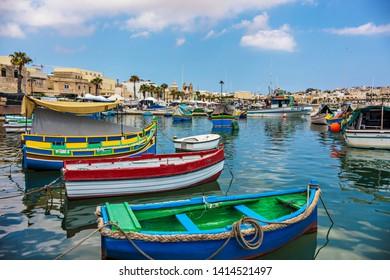 Marsaxlokk, Malta - September 2018: Colorful boats at Maltese fishing village Marsaxlokk, Malta