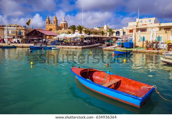 Marsaxlokk, Malta - Traditional colorful maltese Luzzu fisherboat at the old village of Marsaxlokk with turquoise sea water, blue sky and palm trees on a summer day