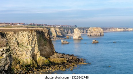 Marsden Bay in South Shields, England UK. View from the cliff tops of the Leas showing Marsden Bay's rocky coastline, Marsden Rock the blue sea and a summer sky.