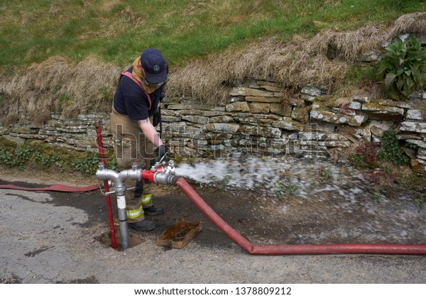 Marsden, Huddersfield, UK - Apr 23 2019: Firefighter checks water supply to control moor fires on moors above Marsden, West Yorkshire