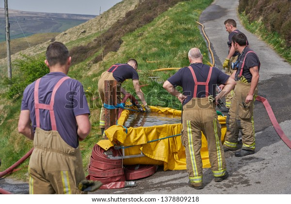 Marsden, Huddersfield, UK - Apr 23 2019: Firefighters secure water supply to control moor fires on moors above Marsden, West Yorkshire