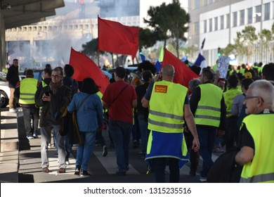 """Marseille, France - February 16, 2019 : Demonstrators with yellow vests (""""gilets jaunes"""" in french) protest against the increase of fuel cost, excessive living costs and high rate of taxes"""