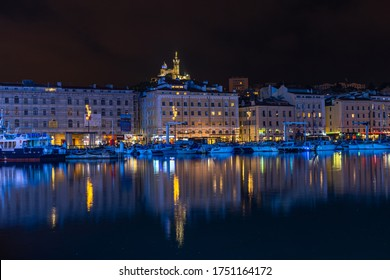 Marseille, France, January 1, 2020 – Cityscape of Marseille Vieux Port (old port) at night with the basilica of  Notre Dame de la Garde in the background