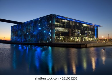 MARSEILLE, FRANCE - MARCH 07, 2014 : Building of  Museum of European and Mediterranean Civilizations (MuCEM) reflecting in water at the evening.