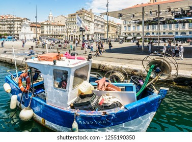 Marseille, France - May 18, 2018: The quai des Belges seen from the basin of the Old Port, one of the busiest place in the city, with an old fishing boat and the mirrored sunshade by Norman Foster.