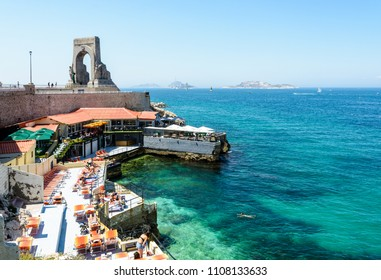 Marseille, France - May 19, 2018: A beach restaurant installed on the shore below the war memorial to the Eastern Army has set up its terrace with parasols and deck chairs on a hot and sunny day.