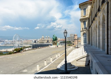 Marseille, France - May 19, 2018: Rear of the Pharo palace with the memorial to heroes and victims of the sea, the Saint-Jean fort, a Ferris wheel and Sainte-Marie-Majeure cathedral in the background.