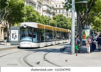 Marseille, France - May 23, 2018: Three-quarter view of a T2 tramway stationing at the Reformes-Canebiere tram station with people walking in the street.