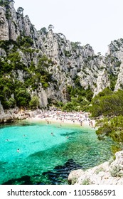 Marseille, France - May 26, 2018: People sunbathing and swimming in the calanque of En-Vau, a natural creek with turquoise water and white sandy beach near Cassis, part of the Calanques National Park.