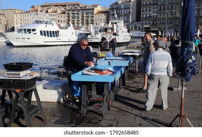 Marseille, France - October 2, 2019: People stand at a stall in the fish market in the old harbor of Marseille, France on October 2, 2019