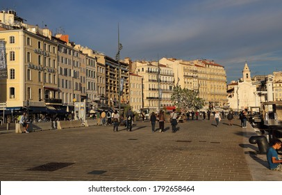 Marseille, France - October 3, 2019: People walking past historical buildings in the old harbor of Marseille in Marseille, France on October 3, 2019
