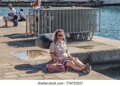 MARSEILLE, FRANCE - September, 2014: woman resting, sitting on a jetty near by the water on a hot sunny day in Marseille, France