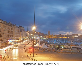 MARSEILLE, FRANCE-SEPTEMBER:  The harbor port of Marseille, France is seen at night with boats and ships as bus goes down cobblestone street in September 2018.