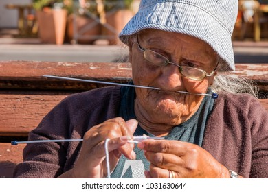 Marseille, Provence, France - June 19 2015 : Old woman knitting and balancing a needle under her nose on a bench on the quay in the old Vieux Port harbour in Marseille