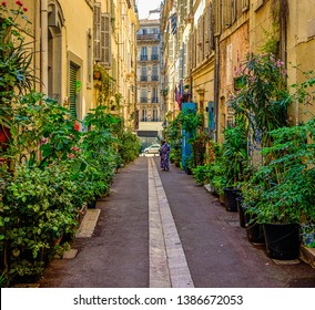 Marseilles, France, 2018, woman standing in an alley decorated with plenty of plants in pots