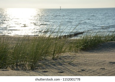 Marsh grass and wooden stages on the beach in North Sea at sunset