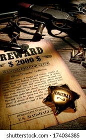Marshall lawman antique brass star badge on old wanted reward fugitive poster with western prison shackles and vintage rifle gun with bullets on law enforcement officer wood desk in sheriff office