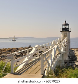 Marshall Point Lighthouse and sailboat sailing on the water in Penobscot Bay with copy space Port Clyde St. George Peninsula, Maine. A beautiful New England summer day with a white wooden light house