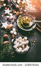 Marshmallow and Christmas star cookies with chocolate and spices: cinnamon, anise and cardamon with nuts on dark background with cozy candle light. Homemade festive sweet gifts preparation.