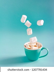 Marshmallow falling into cup over bright turquoise color background