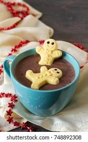 Marshmallow gingerbread men shape taking a warm hot chocolate bath